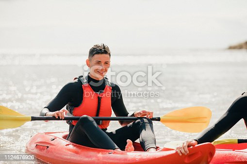 Teenage boy out in the sea on his kayak, with his friends on an overcast day.