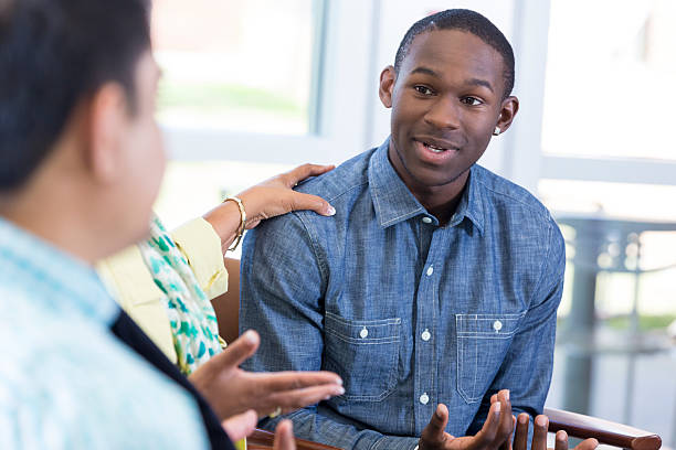 teenage boy explaining something in group meeting - teen counseling stock photos and pictures