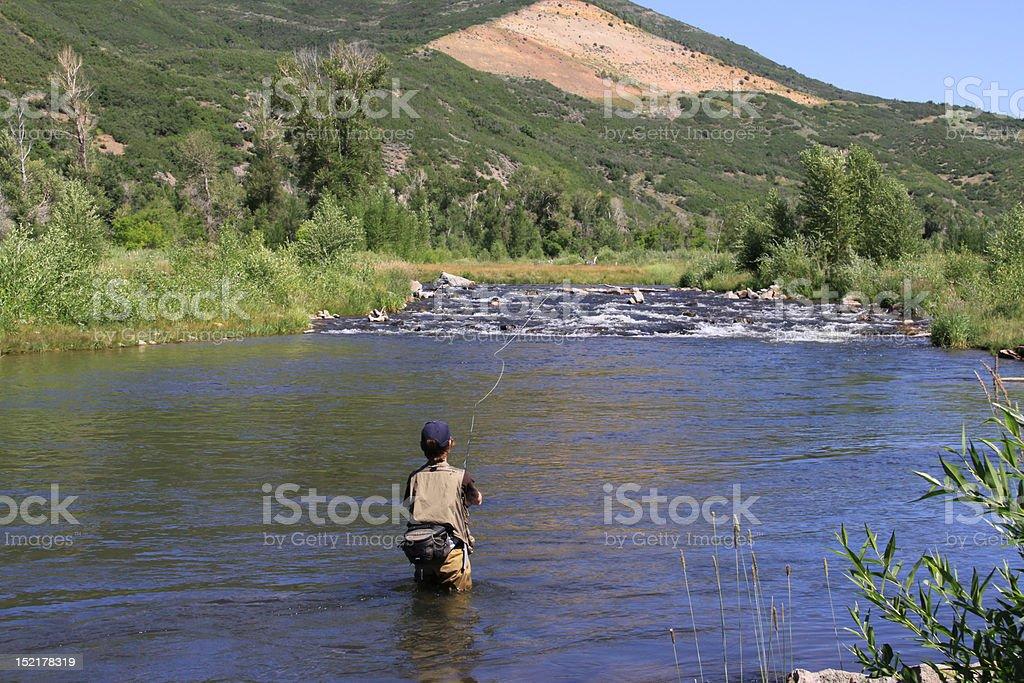 Teenage boy fishing in river stock photo