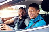 istock Teenage boy having driving lesson with male instructor 1301040523
