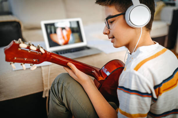 Teenage boy having online guitar lesson stock photo