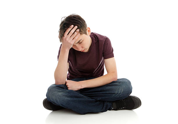Teenage boy headache stress depression A teen boy with one hand in hand showing signs of stress headache or depression. low self esteem stock pictures, royalty-free photos & images