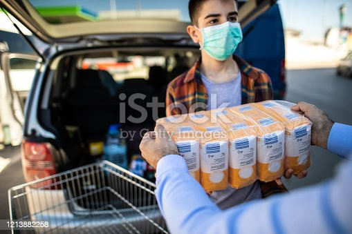 Teenage boy with protective mask helping father to pack flour at car trunk at the moment of virus pandemic