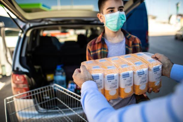 Teenager hilft Vater, Mehl am Kofferraum im Moment der Virus-Pandemie zu packen – Foto