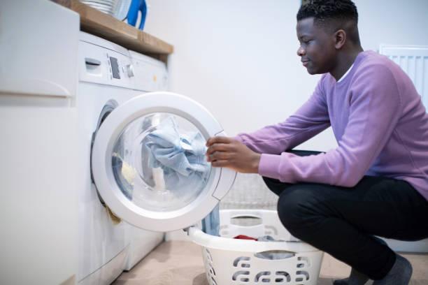 niño adolescente ayudando con las tareas domésticas en el hogar vaciar la lavadora - tarea doméstica fotografías e imágenes de stock
