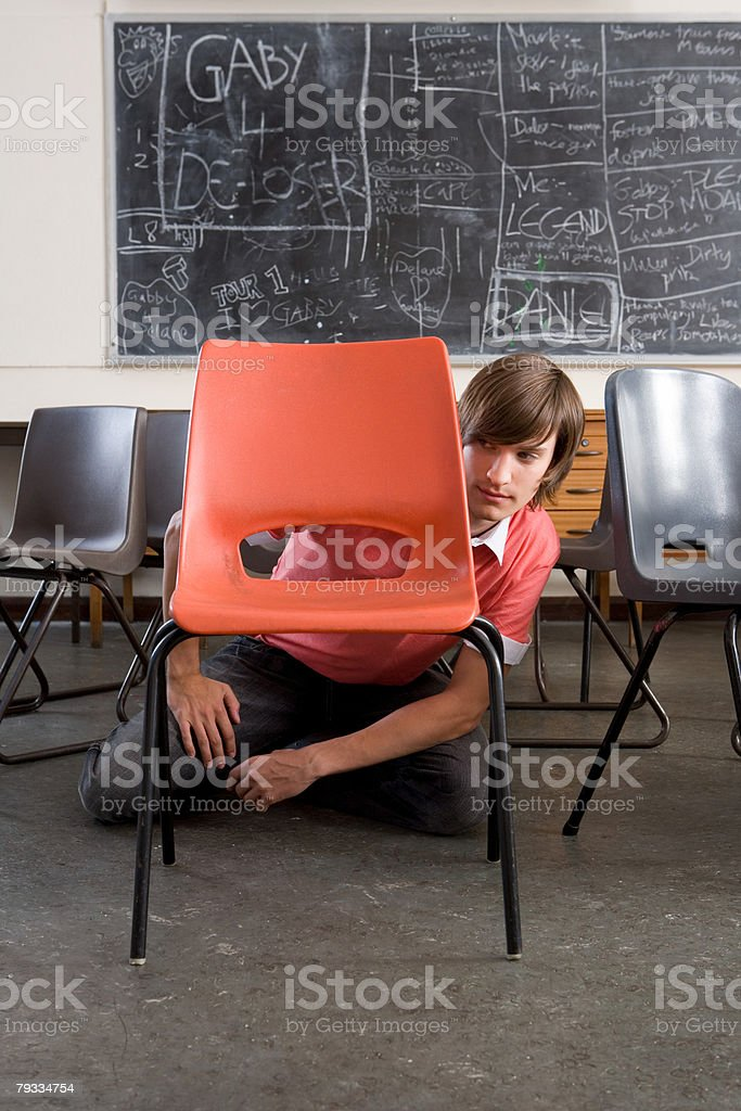 A teenage boy hiding behind a chair 免版稅 stock photo