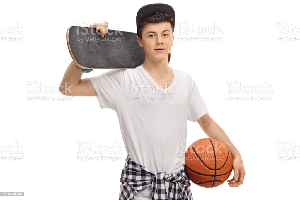 Teenage boy holding a skateboard and a basketball stock photo