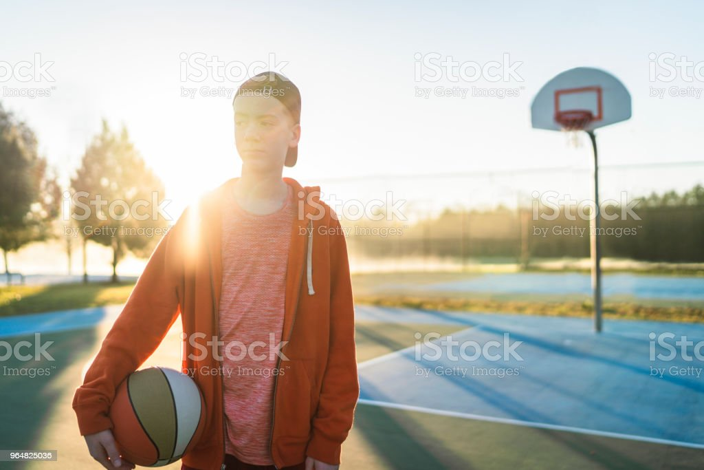 Teenage boy holding basketball at court royalty-free stock photo