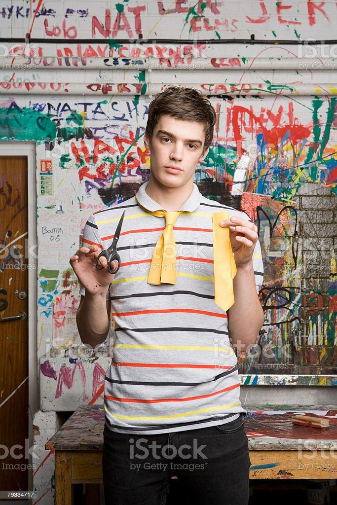 A teenage boy holding half a tie and scissors 免版稅 stock photo
