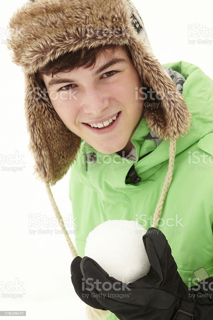 Teenage Boy Holding Snowball Wearing Fur Hat stock photo