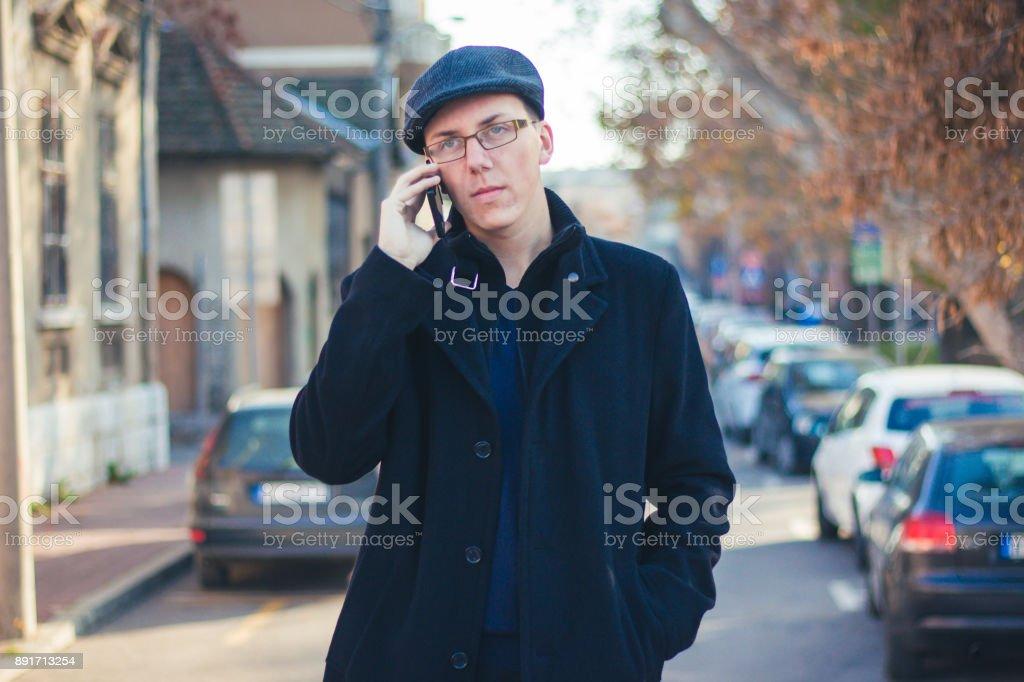 Teenage boy in black coat walk outdoor and using mobile phone.