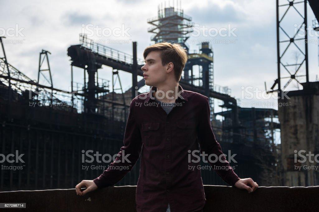 Teenage boy in industrial area stock photo