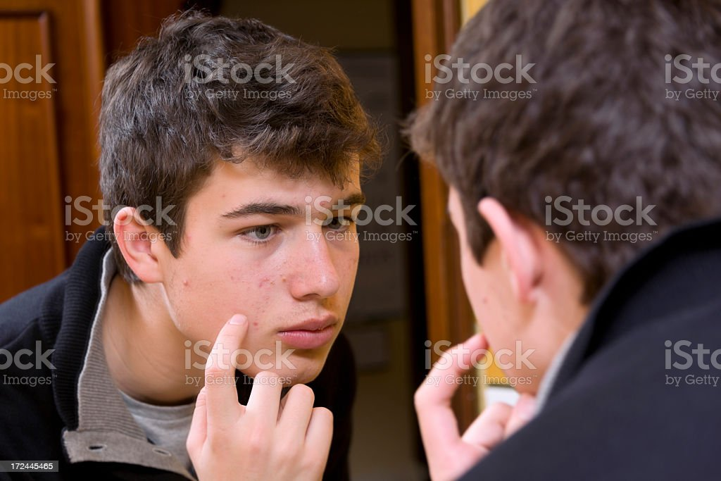 A teenage boy inspects pimples on his cheek in the mirror​​​ foto