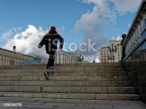 Moscow, Russia - February 24, 2020: Teenage boy is going upstairs to the square