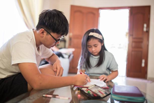 teenager hilft seiner jüngeren schwester bei den hausaufgaben während der covid-19-pandemie. der junge erklärt die fragen auf dem papier. - number 13 stock-fotos und bilder
