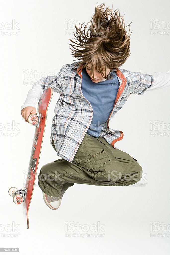 A teenage boy jumping with skateboard 免版稅 stock photo