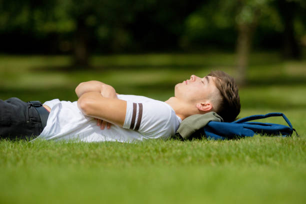 Teenage boy laying on grass on a summers day stock photo
