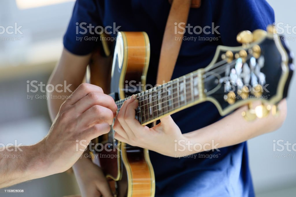 Teenage boy learning electric guitar from trainer Boy playing electric guitar. Student is learning music from male guitarist. They are in training class at conservatory. 12-13 Years Stock Photo
