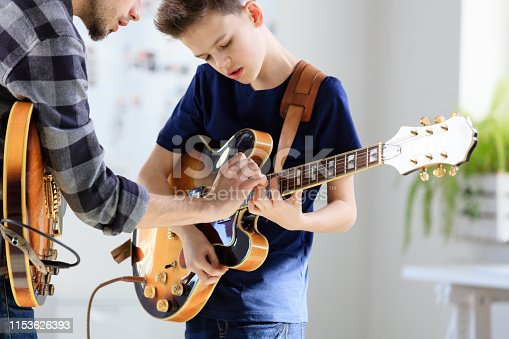 Boy playing electric guitar. Student is learning music from male guitarist. They are in training class at conservatory.