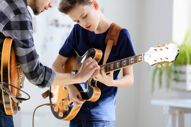 Teenage boy learning electric guitar from trainer stock photo