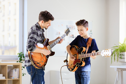 Teenage Boy Learning Electric Guitar From Trainer Stock Photo - Download Image Now