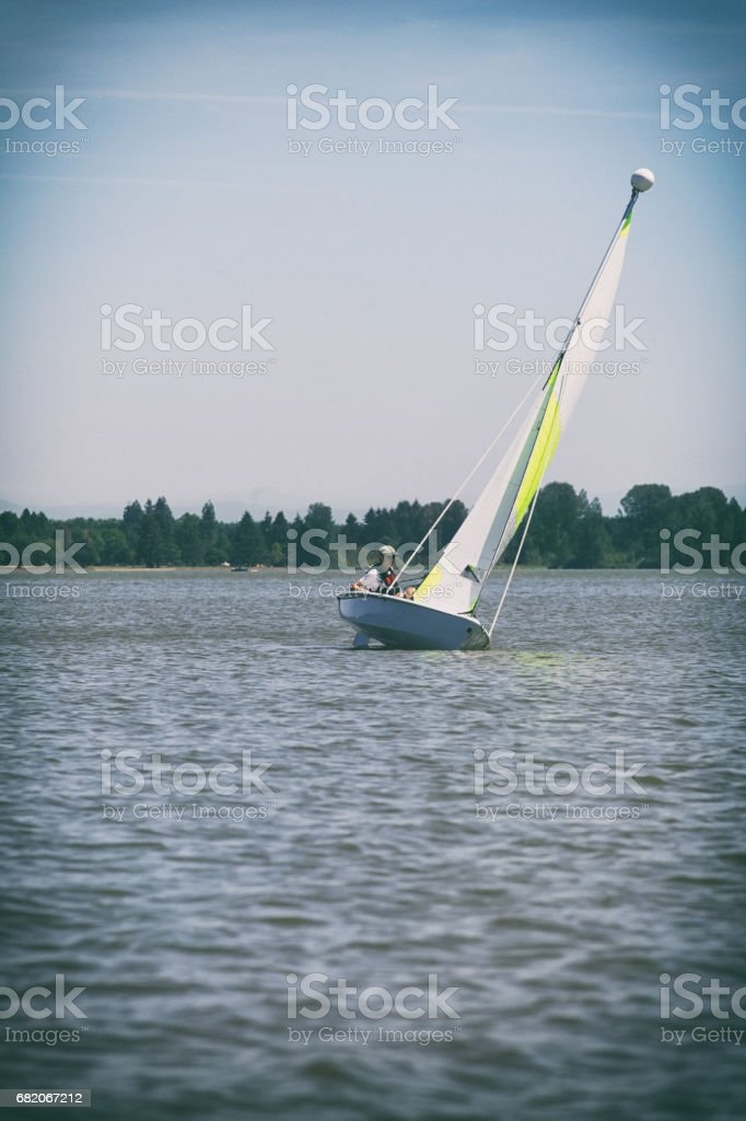 Teenage Boy Learning to Sail in Small Sailboat which is Heeling stock photo
