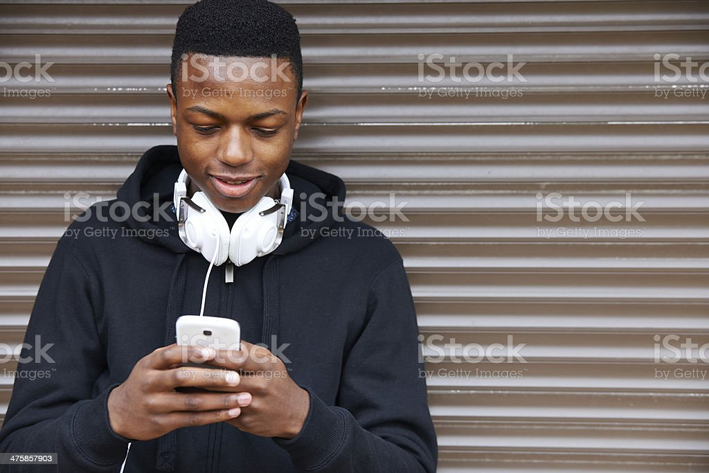 Teenage Boy Listening To Music And Using Phone Pleased to be living in a buzzing city 18-19 Years Stock Photo