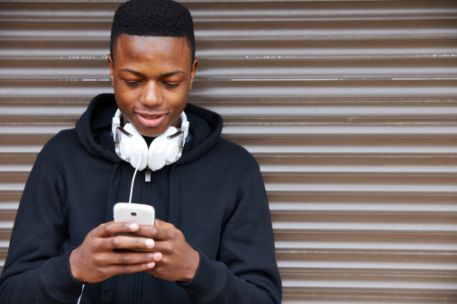 Teenage Boy Listening To Music And Using Phone Stock Photo - Download Image Now
