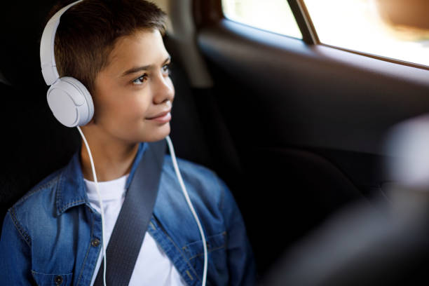Teenage boy listening to music in the car stock photo