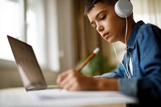 Teenage boy listening to music while doing homework stock photo