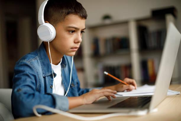 十幾歲的男孩在做作業時聽音樂 - music 個照片及圖片檔