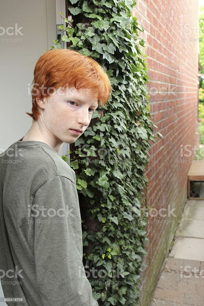 Teenage boy looking moody, walking through door, red hair image stock photo