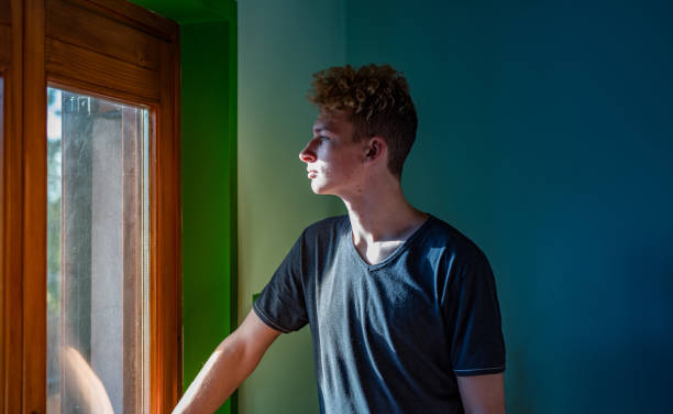 teenage boy looking through the window - boy looking out window stock pictures, royalty-free photos & images