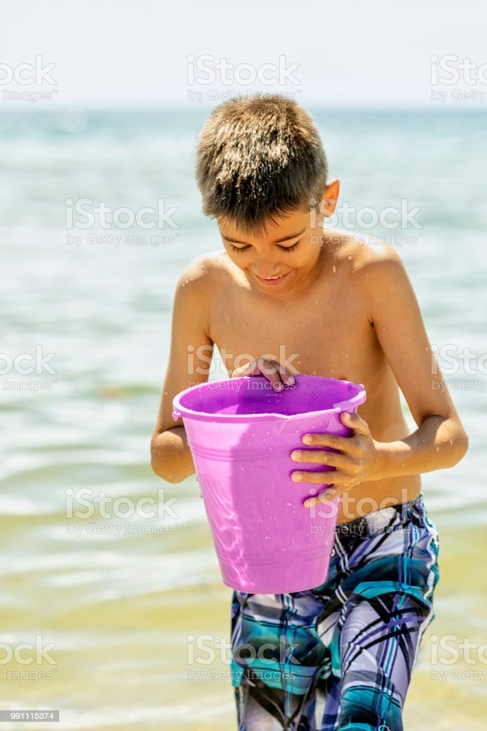 Teenage boy looks down at his bucket where he has captured a crab stock photo