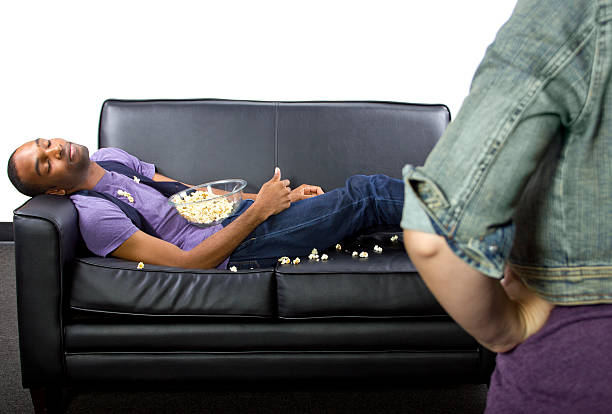Teenage boy napping on a leather couch, spilling popcorn stock photo