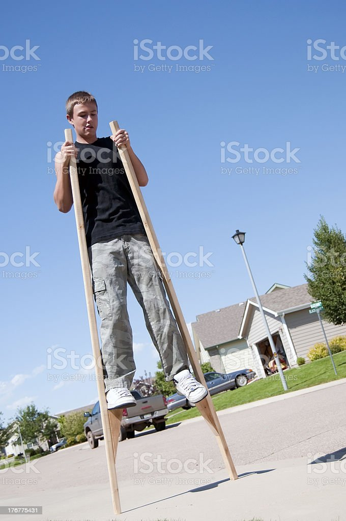 Teenage boy on stilts stock photo