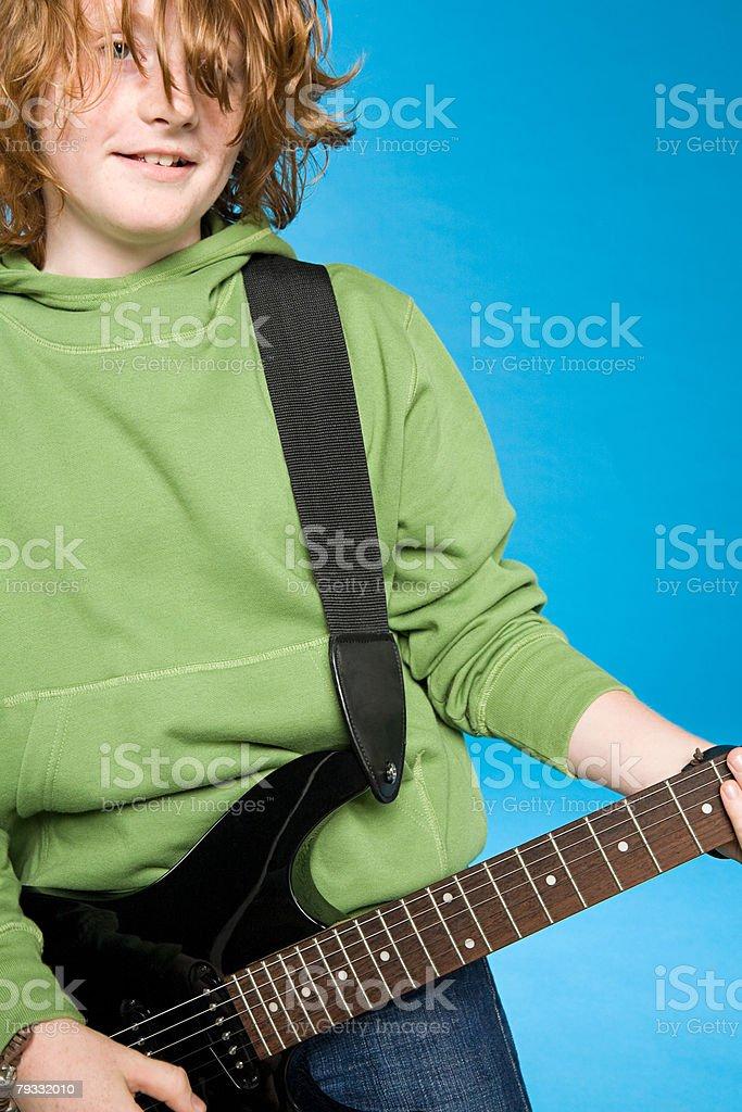 A teenage boy playing a guitar 免版稅 stock photo