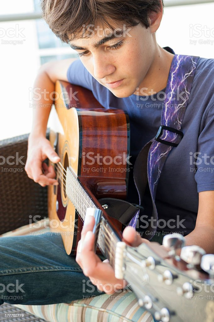 Teenage Boy playing Acoustic Guitar stock photo