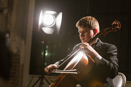 Teenage boy playing double bass in concert