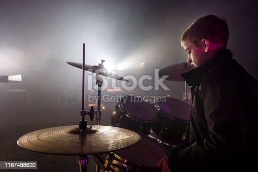 Copy space shot of a teenage boy sitting behind a set of drums and concentrating while playing them at the rock concert.