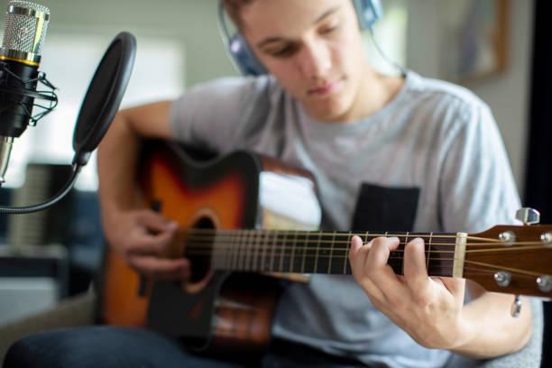 Teenage Boy spielt Gitarre und nimmt Musik zu Hause auf – Foto