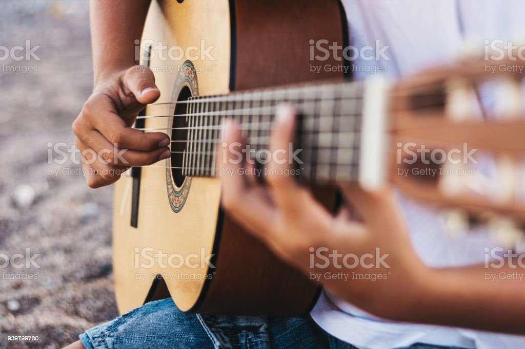 Teenage boy  playing guitar, mid section, low angle view stock photo
