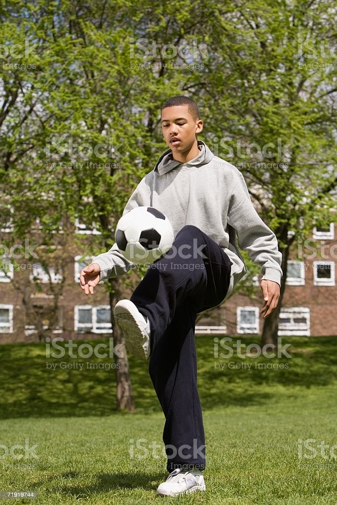 Teenage boy playing keepy uppy royalty-free stock photo