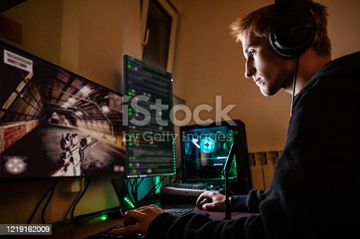 Teenage Boy Playing Multiplayer Games on Desktop Pc in his Dark Room