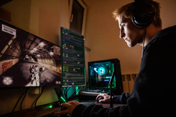 Teenage Boy Playing Multiplayer Games on Desktop Pc in his Dark Room - stock photo Teenage Boy Playing Multiplayer Games on Desktop Pc in his Dark Room computer games stock pictures, royalty-free photos & images