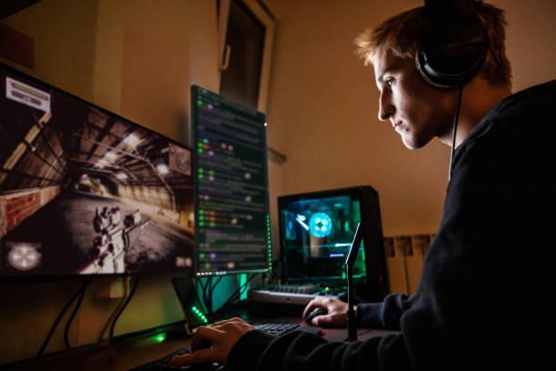 teenage boy playing multiplayer games on desktop pc in his dark room - stock photo - serpentina imagens e fotografias de stock