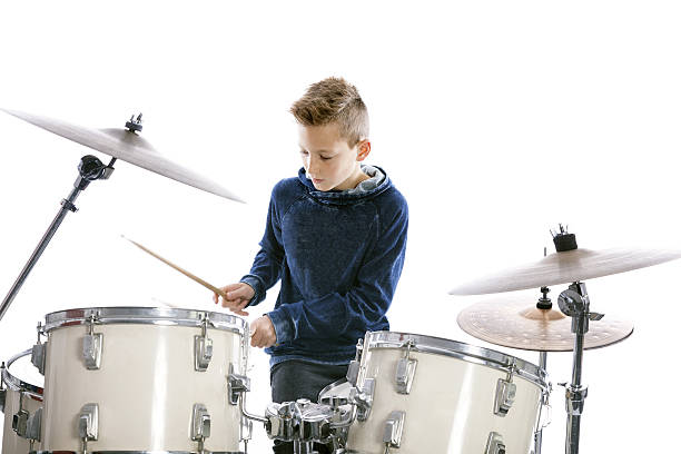 teenage boy plays drums in studio stock photo
