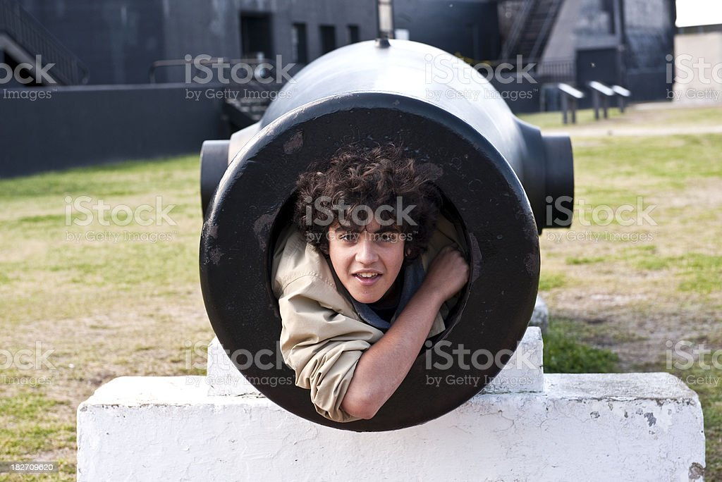 Teenage boy posing inside a cannon stock photo