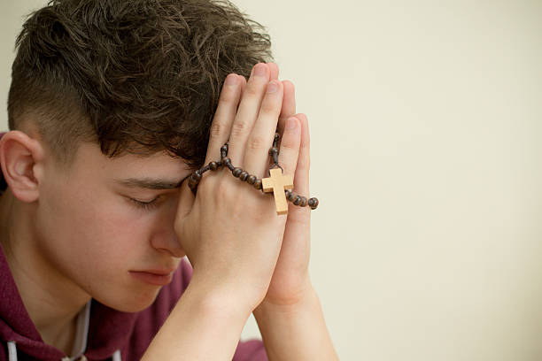 Teenage boy praying with a rosary stock photo
