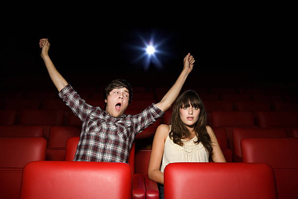 Teenage boy pretending to yawn in the movie theater  bad date stock pictures, royalty-free photos & images